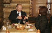 Russian President Vladimir Putin and his wife, Lyudmila, toast in a restaurant they visited after voting in Moscow. Russians voted Sunday in an election in which Putin's party claimed a commanding share of parliamentary power.