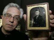 Wes Cowan holds a daguerreotype of abolitionist John Brown at his auction house in Cincinnati. The print of the abolitionist was bought Friday for $97,750, Cowan said.
