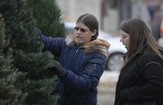 Lawrence residents Lindsay Williamson, left, and her mother, Wendie Wilcken, move through the selection of pines at Luncheon Optimist Christmas Trees. The site is in the parking lot of Checkers, 2300 La.