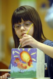 Addie Wendel, 8, puts a lot of thought into the birdhouse she's painting at Hilltop Child Development Center on the Kansas University campus. The birdhouses will be auctioned off and the proceeds given to needy families at Hilltop to help with holiday expenses.