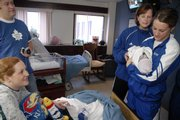 New parents Ben and Heidi Nelson, left, get a visit from Kansas University women's basketball coach Bonnie Henrickson, second from right and player Katie Smith, a junior from Omaha, Neb., who holds the Nelsons' 1- day-old son, Finn, on Tuesday at Lawrence Memorial Hospital. The women's basketball team visited patients and passed out Jayhawk gifts on their annual holiday tour of LMH.