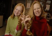 Morgan Linder and her mother, Renee Linder, of Baldwin City, display the hair they recently cut off for the Locks of Love program, which donates hair to children who have lost theirs because of illness.