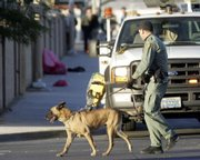 A police officer and dog walk through a crime scene Tuesday in Las Vegas. Assailants shot six young people Tuesday who had stepped off a bus coming from a high school, wounding two seriously, in a midday attack just blocks from two elementary schools, authorities said.