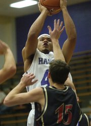 Haskell senior Vince Baccus puts up a shot over Calvary's Chris Miller. The Indians rolled, 116-51, Thursday at Haskell.
