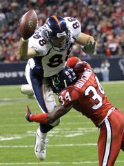 Denver Broncos tight end Tony Scheffler (88) leaps for the end zone as Houston Texans defensive back Von Hutchins (34) defends. The Texans beat the Broncos, 31-13, Thursday in Houston.