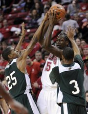 Forward James Gist, center, tries to get away from Ohio's Justin Orr (25) and Michael Allen (3) during the first half of Ohio's shocking victory over Maryland on Wednesday in College Park, Md.