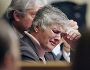 Raynella Dossett Leath, 59, weeps as she listens to prosecutors Friday in Knoxville, Tenn., talk about circumstances surrounding the death of her then-husband, District Attorney Ed Dossett, who was found dead in his cattle lot in 1992. Investigators thought the herd had accidentally trampled him to death. Now they believe the trampling may have covered up his murder for 15 years.