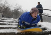 Will Burg, 15, of Lawrence, takes some stairs Saturday while sledding near Kansas University's Memorial Drive. At right is Dylan Brooks, 16.