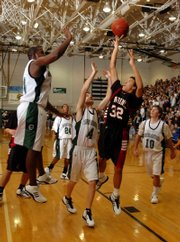 Lawrence High's Dorian Green lofts a shot over Free State defenders Anthony Russell, center, and Christian Ballard in this file photo from last Dec. 21.