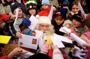 "A Santa Claus impersonator is surrounded by children at the Christmas Post Office in Himmelpfort, which means ""Heavens Gate,"" in northern Germany. Germany&squot;s postal service runs two special post offices to handle and answer children&squot;s wish lists to Santa."