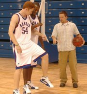 Kansas University's Matt Kleinmann (54) and Darnell Jackson give Journal-World sports writer/KU walk-on hopeful Jesse Newell some post-up pointers. Newell hopes to put the advice to good use during walk-on tryouts Sunday.
