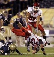 Utah's Ray Stowers (24) dives for a first down as teammate Freddie Brown leaps over the play during the first quarter of the Poinsettia Bowl. Utah won the first bowl game of the season, 35-32, over Navy on Thursday in San Diego.