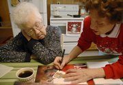 "Patty Hoover helps her mother sign cards to accompany Christmas gift calendars for their family in this 2007 file photo. After Hoover&squot;s father died, the family realized that he had been covering for his wife&squot;s forgetfulness. ""If you live out of state and don&squot;t come back very often, you are so excited about seeing them that you may not see those signs,"" said Hoover, who now lives in Eudora with her mother."
