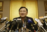 "Former Thailand Prime Minister Thaksin Shinawatra speaks today at a news conference in Hong Kong. Thaksin said he will ""explore options"" in February about a return to Thailand but will not resume his career in politics after being ousted in a bloodless coup d&squot;etat last year."