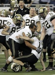 Purdue kicker Chirs Summers (13) is mobbed by teammates after hitting a 40-yard field goal as time expired. The kick lifted Purdue to a 51-48 victory Wednesday in the Motor City Bowl in Detroit.