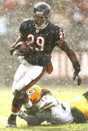 Chicago running back Adrian peterson, top, carries the ball in a snow squall past Green Bay's Atari Bigby. Quarterback Brett Favre said Wednesday the weather flummoxed the Packers, the youngest team in the NFL, in their 35-7 loss Sunday in Chicago.