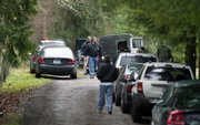 King County Sheriff Deputies gather near a rural property east of Seattle where six people, likely three generations of a family, were found dead Wednesday in Carnation, Wash.