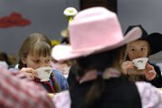 Hazel Ingram, 8, left, and Saya Eagleman, 8, sip tea Friday during the holiday tea party at Lawrence Public Library, 707 Vt. The party's theme was Western. Live music and a roping demonstration were among the activities.