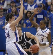 Kansas' Sasha Kaun and Russell Robinson crowd Yale's Ross Morin on Saturday, Dec. 29, 2007 at Allen Fieldhouse.