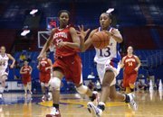 Kansas senior Taylor McIntosh (13) brings the ball downcourt against Boston University's Jesyka Burks-Wiley on a fast break. McIntosh led the Jayhawks to a 71-57 victory Sunday at Allen Fieldhouse.