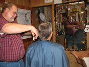 Basehor barber Paul Runnels cuts Piper resident Vearl Jones' hair recently at Hair Mechanix. Runnels' father, Dwight Runnels, who died Dec. 10, opened the shop in Basehor more than 40 years ago.