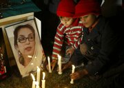 Pakistani children participate in a candle-lit ceremony in memory of slain opposition leader Benazir Bhutto in Lahore, Pakistan. Pakistan's election commission on Tuesday postponed next week's parliamentary voting until February.