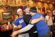 Kansas fans, from left, Sam Engleman, Nick Vaughan and Danny Lenz hug after watching the KU-Virginia Tech Orange Bowl game on TV Thursday at Jefferson's Restaurant, 743 Mass. Celebrating KU fans crowded the streets of downtown following the historic win.