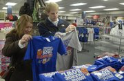 Laura Skinner and Ryan Kunhart, both of Nebraska, were in Lawrence Friday checking out Kansas University and decided to shop for some Orange Bowl memorabilia at the Jayhawk Bookstore at 1420 Crescent Road. Within hours of the Jayhawks' 24-21 victory Thursday night against Virginia Tech in the Orange Bowl, fans began their rush on local bookstores and sporting goods stores for mementos of the historic victory. Managers reported sales comparable with a KU Final Four appearance.