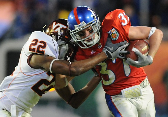 Kansas receiver Micah Brown is pushed out of bounds by Virginia Tech cornerback Stephan Virgil after successfully pulling in a reception on a fake punt attempt in the second half of the Orange Bowl Thursday, Jan. 3, 2007 at Dolphin Stadium.