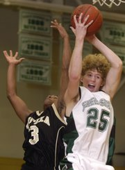 Free State junior Chase Hoag (25) rips down an offensive rebound against Topeka High's A.J. Barber on Saturday at FSHS.