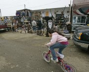 A child pedals her bike in front of shops in the Puerto Nuevo area of Rosarito, Mexico. Recent violence has contributed to a dramatic drop in tourist business in the area, which is on the Baja California peninsula, south of San Diego.