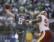 Seattle quarterback Matt Hasselbeck (8) unleashes a pass under pressure from Washington's Phillip Daniels. The Seahawks defeated the Redskins, 35-14, on Saturday in Seattle.