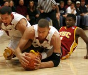 Stanford's Mitch Johnson, left, and Brook Lopez, center, go after a loose ball at the legs of Southern California's Angelo Johnson. 