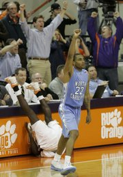 North Carolina's Wayne Ellington (22) reacts after making the winning three-pointer while Clemson's James Mays slams into press row after trying to block the shot. UNC won in overtime, 90-88, Sunday in Clemson, S.C.