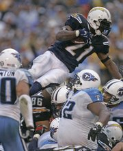 San Diego Chargers' Ladainian Tomlinson goes over the top for a one-yard touchdown in the fourth quarter. The Chargers beat the Tennessee Titans, 17-6, Sunday in San Diego to advance in the AFC playoffs.