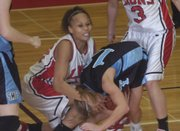 Lawrence High junior Tania Jackson, left, battles for a possession against Shawnee Mission East. The Lions suffered their first setback of the season, 48-40, on Tuesday night at LHS.