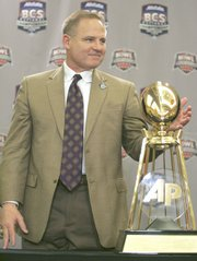 LSU coach Les Miles poses with the Associated Press College Football National Championship Trophy. Miles collected the hardware Tuesday in New Orleans.