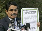 San Francisco Zoo Director Manuel Mollinedo holds a poster that will be displayed around the zoo warning patrons not to taunt animals in this Jan. 2 file photo. Since the deadly tiger attack, the zoo and Mollinedo have come under scrutiny and criticism for his past record and his handling of the escape: essentially blaming the victims and accusing them of taunting the tiger that broke loose.