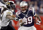 New England running back Laurence Maroney, right, rushes past Jacksonville's Terry Cousin. The Patriots defeated the Jaguars, 31-20, on Saturday night in Foxborough, Mass.