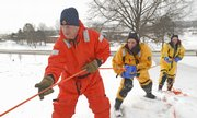 Lawrence-Douglas County Fire and Medical personnel, from left, Rick Laughlin, TIm Childers and John Hawkins pull stranded co-workers from the ice during an ice training exercise on Friday, January 18, 2008 at the West Campus Pond at Kansas University.  Below freezing temperatures provided the perfect environment for the annual ice training exercise.
