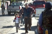 A child is evacuated by a policeman from a battle with gunmen during a shootout Thursday in Tijuana, Mexico. Soldiers, state and local police were sent in to help control the three-hour confrontation that began when federal agents tried to raid a house, authorities said.