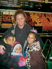 Krissy Yeadon shops with her children, from left, Stavan, 7, Marquis, 5, and Diamond Yeadon, 7, Thursday at Checkers Food Store. Yeadon says she will use her tax rebate to pay off some bills.