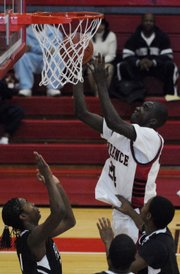 Lawrence High's Baba Diallo shoots over Hogan Prep's defenders at Lawrence High School.