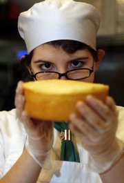 Maria Del Mar Baez, a student at Johnson & Wales University, checks the level of a cake while interning Wednesday at Johassen's Bakery Cafe in Providence, R.I. Johnson & Wales University, which runs the bakery, has started phasing out trans fats in its restaurants, hotels and dining services on campuses in Providence, North Miami, Fla., Denver and Charlotte, N.C., and plans to be trans fat-free by the fall semester.