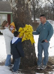 Lt. Col. Pat Cook, right, helps take down the yellow ribbon that his in-laws, Carol and Jim Murray, of Lansing, hung in his honor during his 15-month deployment to Afghanistan. Cook's wife Wendy, from left, his sons Casey, 10 months, and Chase, 8, helped remove the ribbon.