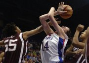 Texas A&M's Danielle Grant (55) fouls KU freshman Krysten Boogaard on Saturday, Jan. 26, 2008 during the Jayhawks' basketball game at Allen Fieldhouse.