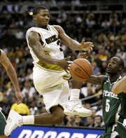 Missouri's Stefhon Hannah loses the ball as Michigan State's Travis Walton (5) defends during a basketball game in this Nov. 19, 2007, file photo in Kansas City, Mo. Hannah remained hospitalized Monday with a broken jaw after a weekend brawl outside a nightclub.