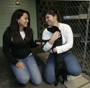 Sady Lima, left, and Cecilia Martinez hug a puppy that has been put up for adoption at the Stockton Animal Shelter in Stockton, Calif. In Stockton, Modesto and other nearby cities with some of the highest foreclosure rates in the nation, animal shelters and rescue groups are inundated with animals orphaned when their owners lose their homes.