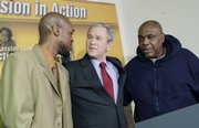 President Bush puts his arms around Adolphus Mosely, left, and Tom Boyd, two recent graduates of the Jericho Program during his visit and tour of the center Tuesday in Baltimore.