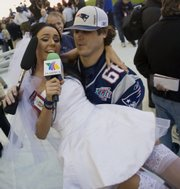 Ines Gomez Mont, left, a reporter from TV Azteca in Mexico, is carried off in a wedding dress by  New England center Lonie Paxton. Gomez Mont dressed up to ask Patriots quarterback Tom Brady to marry her at Super Bowl XLII media day Tuesday in Glendale, Ariz.